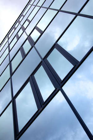 gevel van het kantoorgebouw met bewolkte hemel weerspiegeld