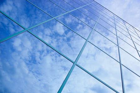 reflecties van wolken en blauwe hemel in gevel van het kantoorgebouw Stockfoto