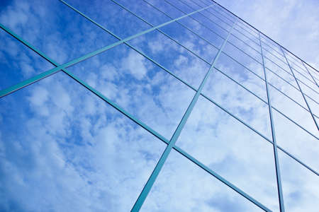 window panes: reflections of clouds and blue sky in facade of office building Stock Photo