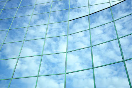 reflections of blue sky and clouds in curved facade of office building