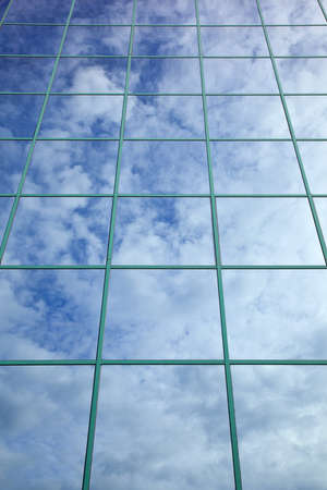 clouds and blue sky reflected in glass facade of office building Stock Photo
