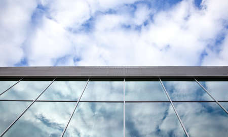 clouds and blue sky reflected in windows of office building
