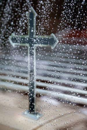 hearse: cross seen through hearse window full of raindrops Stock Photo