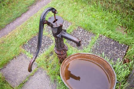 oude natte gietijzeren waterpomp in de tuin Stockfoto