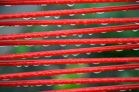 part of red summer chair with raindrops and green background photo
