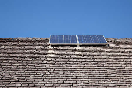 old roof with wooden tiles and solar energy panels photo