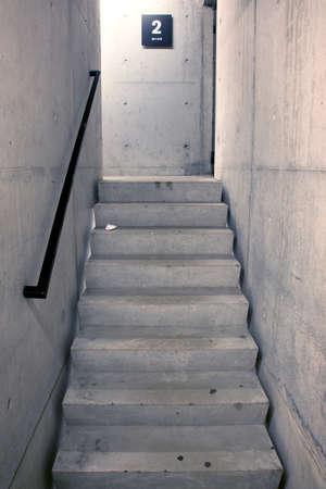 concrete staircase and stairs leading upwards to second floor of parking garage photo