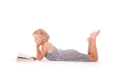 young girl reads a book lying down on the floor of studio against white background photo