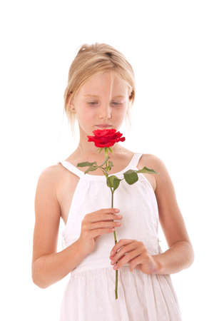 young girl in white dress smelling a red rose against white background photo