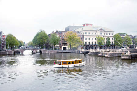 amstel: old boat on river Amstel near Theater Carr� in Amsterdam