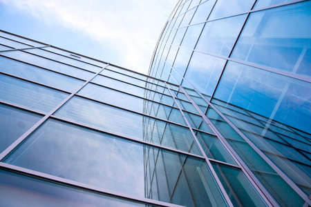 facade of modern glass blue office and sky with clouds reflected photo