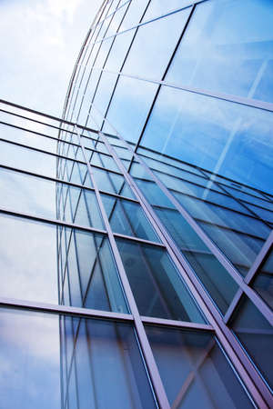 vertical imgage of facade of modern glass blue office and sky with clouds reflected Stock Photo