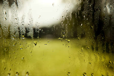 background consisting of wet windshield with rain drops and green white background Stock Photo