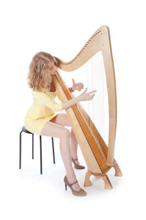 young woman in sexy yellow mini dress playing the harp photo