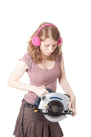 inexperienced: young pretty woman with circular saw against white background