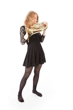 french horn: young woman in black playing  french horn against white background