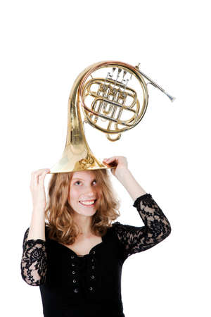 french horn: young woman playing with french horn against white background Stock Photo