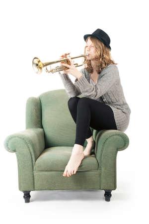 白い背景の肘掛け椅子でトランペットを演奏若いきれいな女性