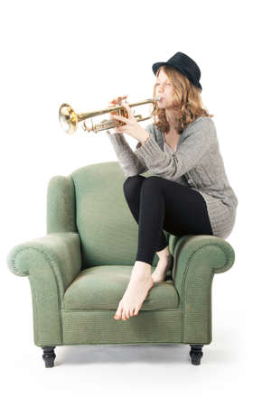 young pretty woman playing the trumpet on armchair against white background Stock Photo