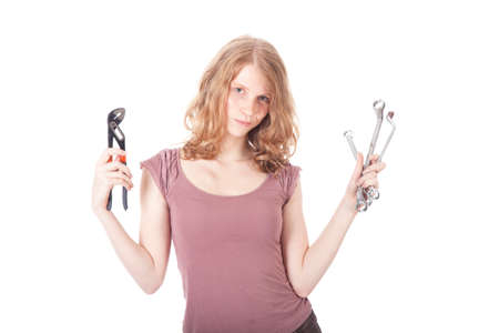 young pretty woman with ring spanners and pipe wrench against white background photo