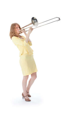 young woman in yellow playing trombone and white background