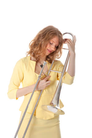 young woman with trombone against white background photo
