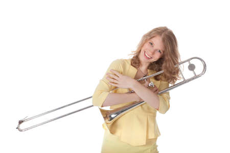 young woman in yellow holding trombone and white background photo