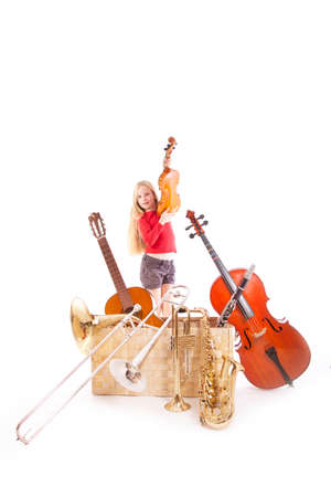 young girl with many musical instruments in box against white background