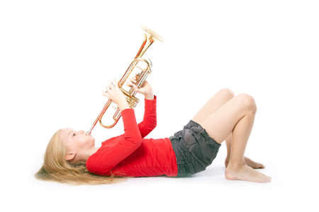 young girl in red playing trumpet laying down against white background