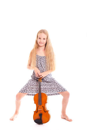 young girl in dress standing with her violin against white background photo