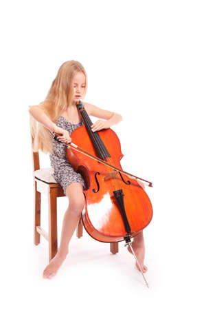 young girl in dress playing cello against white backgound photo