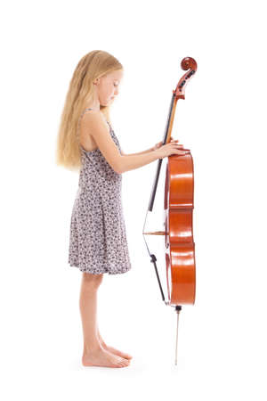 young girl in dress and her cello standing in studio against white background photo