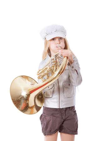 jong meisje met pet spelen hoorn tegen een witte achtergrond Stockfoto