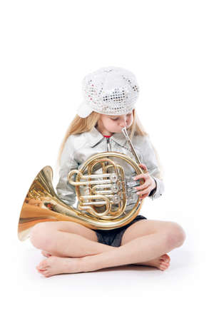 sitting young girl with cap playing french horn against white background