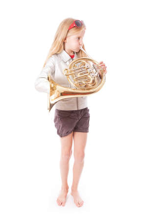 young girl playing french horn against white background