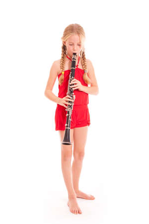 young girl in red playing clarinet against white background