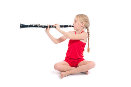 young sitting girl in red playing clarinet against white background photo