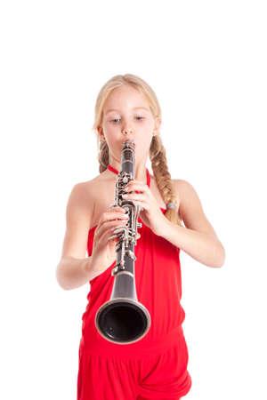 clarinete: ni�a en clarinete tocando rojo sobre fondo blanco Foto de archivo