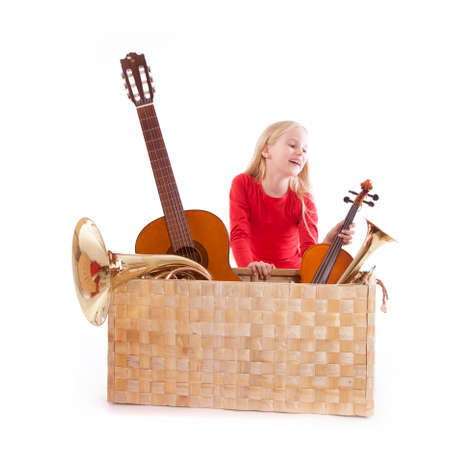 young girl with musical instruments in box against white background photo