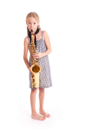 young girl in dress and her saxophone standing in studio against white background