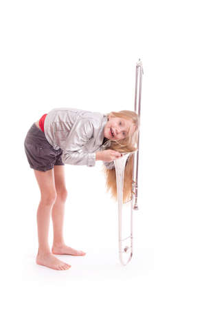 young girl in silver jacket having fun with trombone in studio against white background Stock Photo