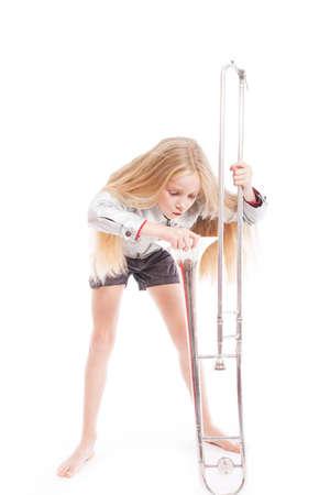 白い背景のスタジオでトロンボーンを見る若い少女 写真素材