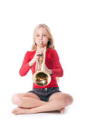 young girl in red playing trumpet against white backgound
