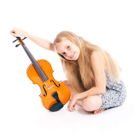 young girl in dress happy with violin in studio against white background photo