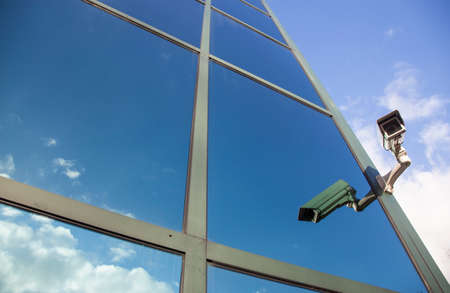 camera on glass facade of office building reflecting clouds and blue sky photo