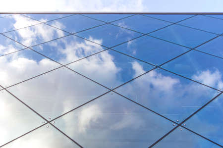 reflexions of clouds and blue sky in glass facade of modern building
