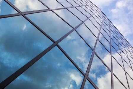 reflexions of clouds and blue sky in diagonal glass facade of modern building