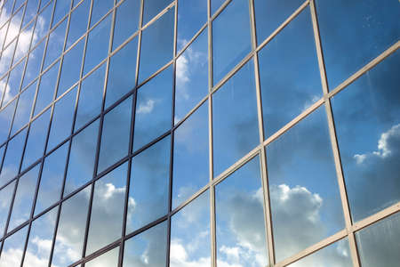 reflexions of clouds and blue sky in  glass facade of modern building photo