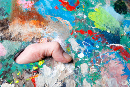 brushwork: colorful palette full of paint spots and thumb