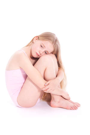young girl in pink with sad expression sitting on floor of studio against white background photo